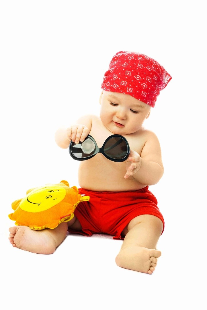 Baby in red bandana and shorts trying on sunglasses
