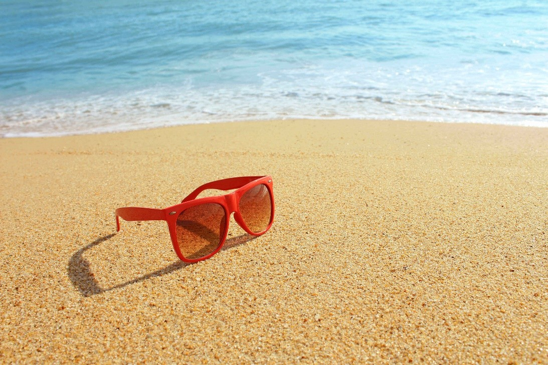 Red sunglasses on a sandy beach