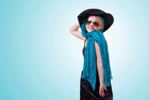 Young girl wearing black hat, sunglasses and head scarf